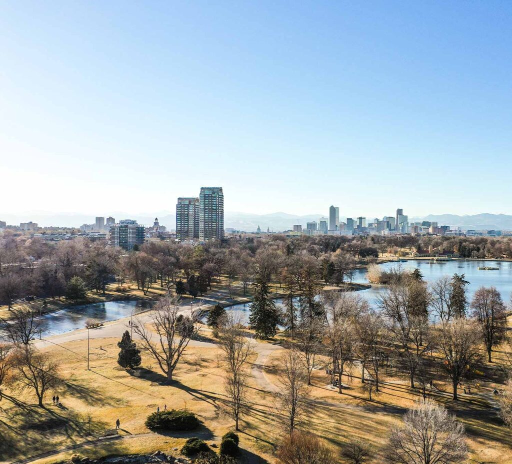 An image of Denver, CO with a park, lakes and the city and mountains in the background