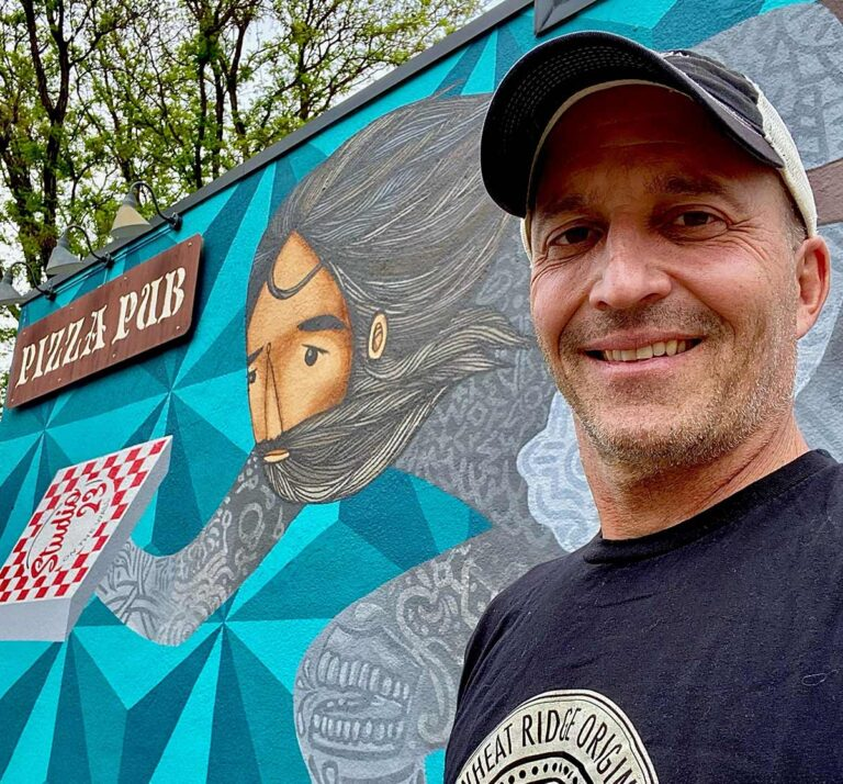 Mark Eskow, Owner of Right Coast Pizza in Wheat Ridge, stands in front of a mural