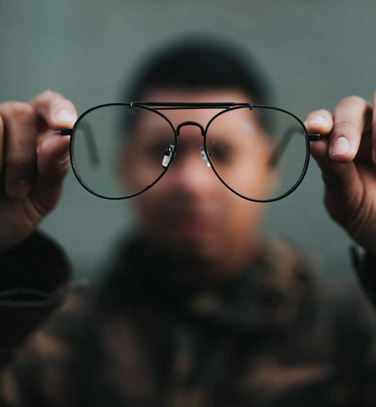 A man holds glasses and the image is blurred