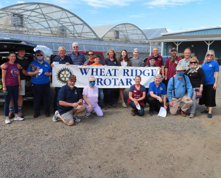 The Wheat Ridge Rotary club volunteers stand outside of a greenhouse